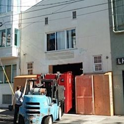 A forklift begins lowering the beast into Hi Lo's basement.