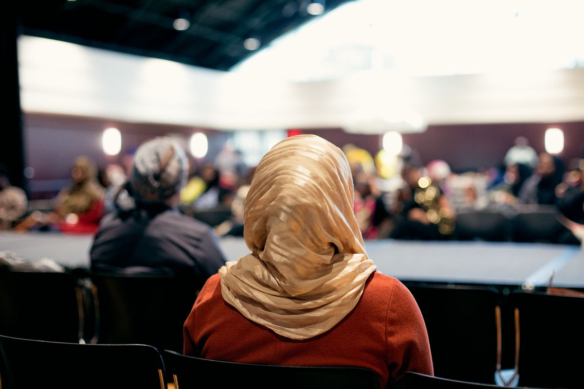 A woman in a hijab sits to watch a fashion show at the Headwrap Expo