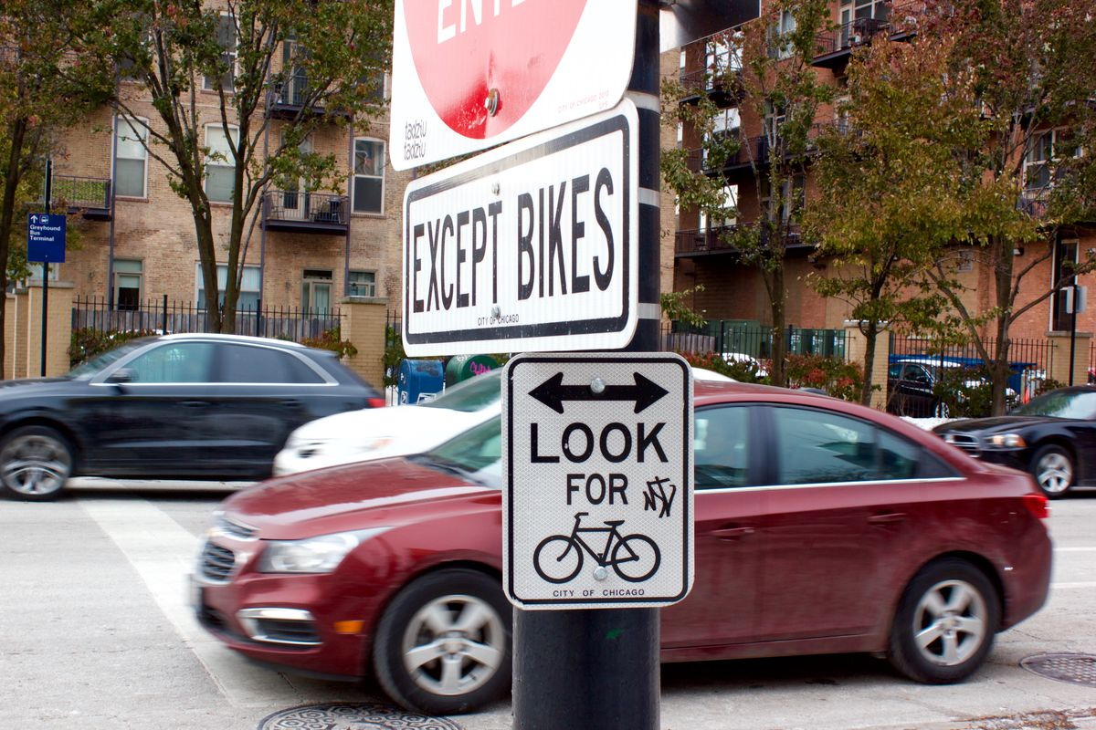 Posted traffic signs remind drivers to watch for bicyclists Wednesday at Harrison and Clinton streets.