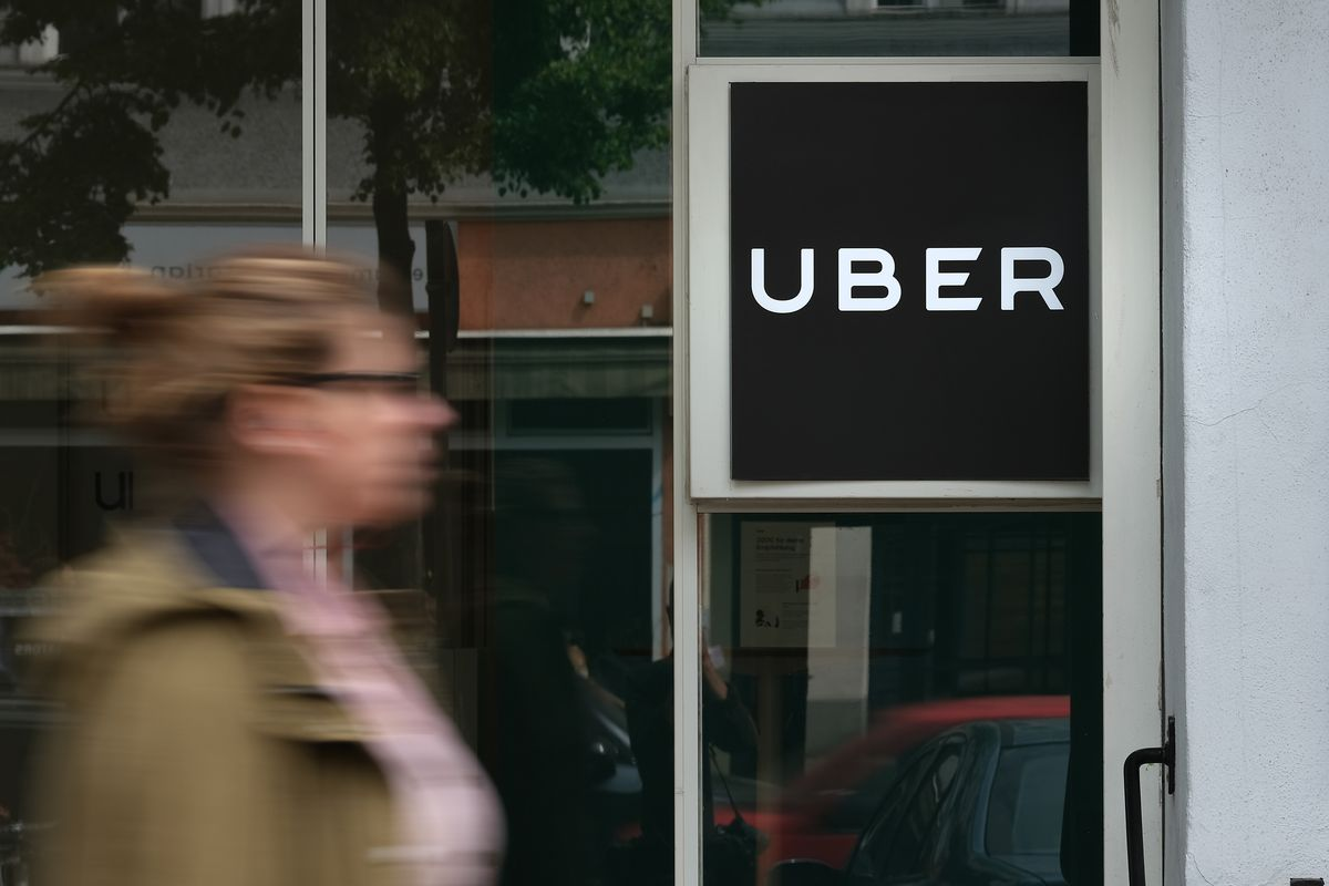 A woman walks past an Uber sign