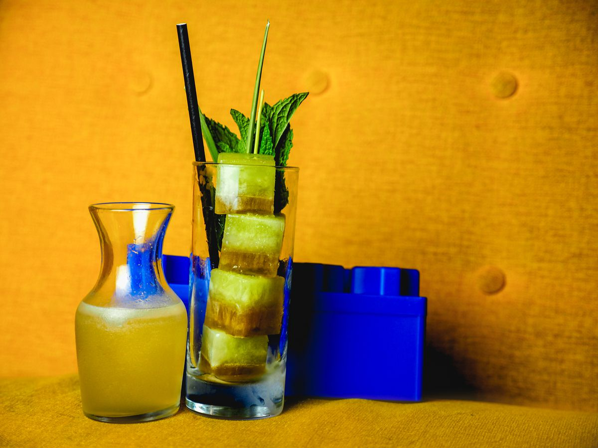A highball with pineapple cubes with a blue oversize Lego block.