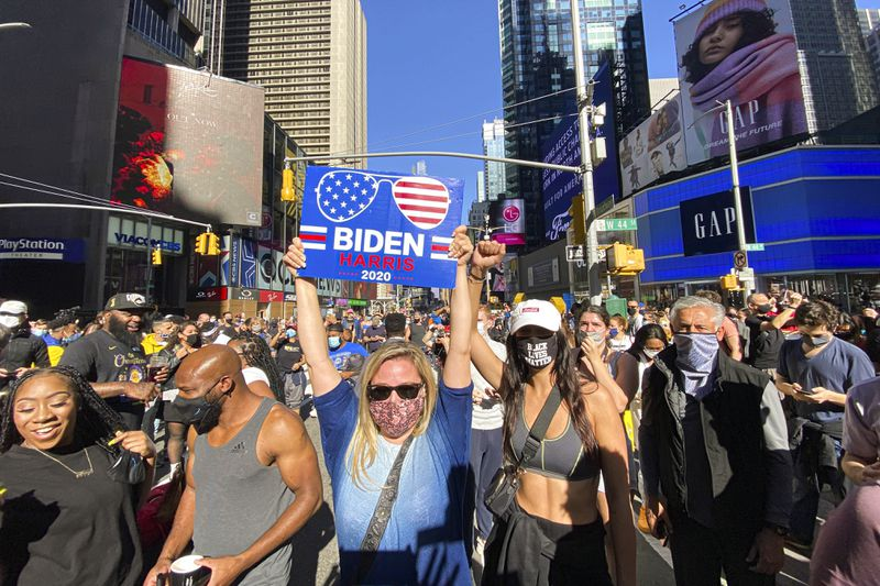 The neon billboards glow in the sunshine above the packed square — all sorts of people, most in masks, celebrate together; the front of the photo has a Black couple, the woman in black, and the man in grey, standing next to a white woman in sunglasses, holding a sign above her head that says 'Biden Harris 2020,' that features Biden's trademark aviators. Beside her is a woman in a mask that reads 'Black Lives Matter,' her fist raised to the sky.