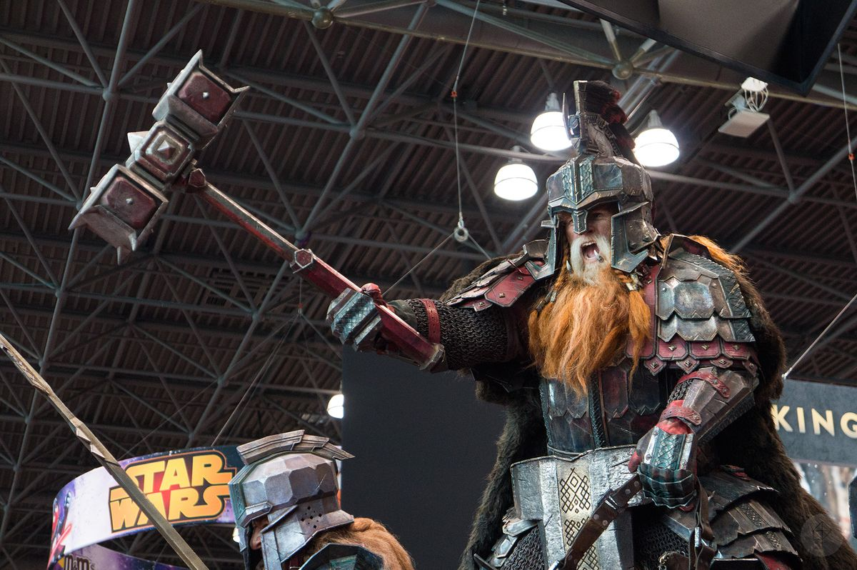 a model of a dwarf wielding a dual-headed mace perched above the Weta Workshop booth at NYCC 2015