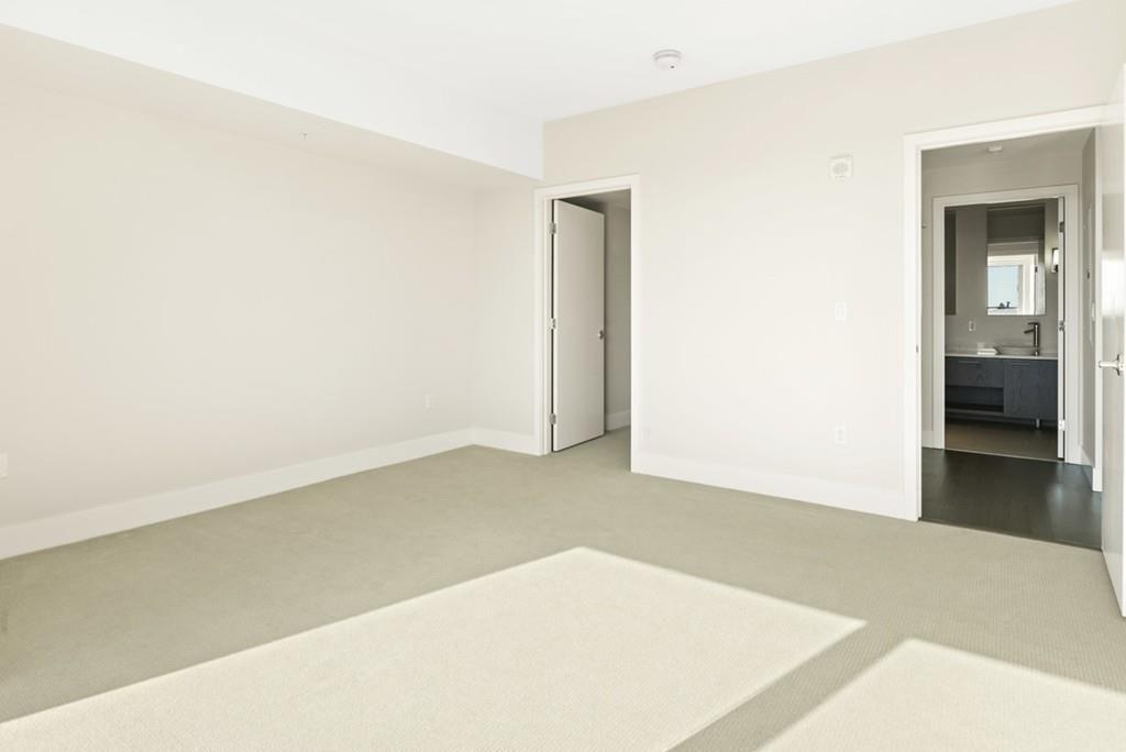 An empty bedroom with the door to the bathroom opened.