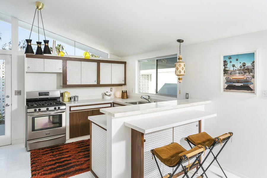 A midcentury modern kitchen with white cabinetry, walls, and flooring. There is an orange and black area rug.