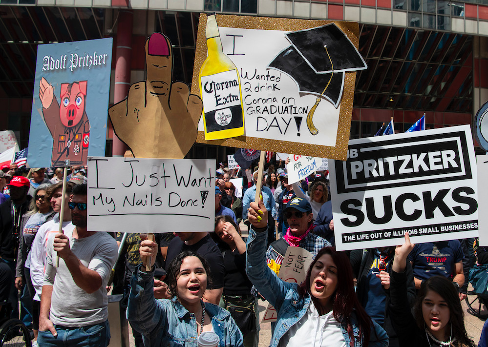 Reopen Illinois protesters pictured Saturday in the Loop. Some signs compared Gov. J.B. Pritzker to Adolf Hitler.