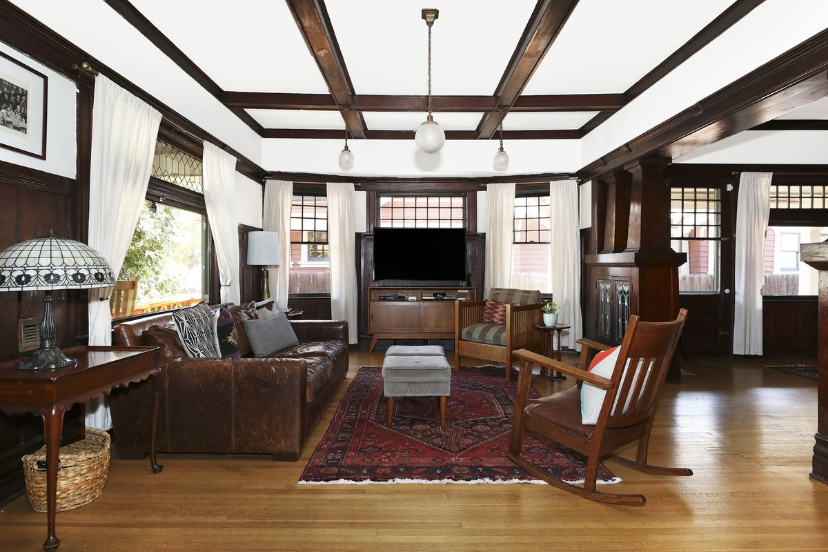 A photo of a wood-floored living room with dark wood ceiling beams.