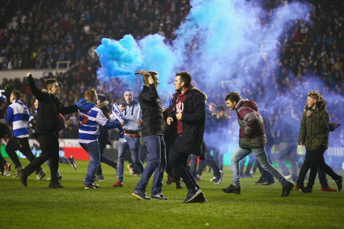 Reading fans celebrate on the pitch after the final whistle.