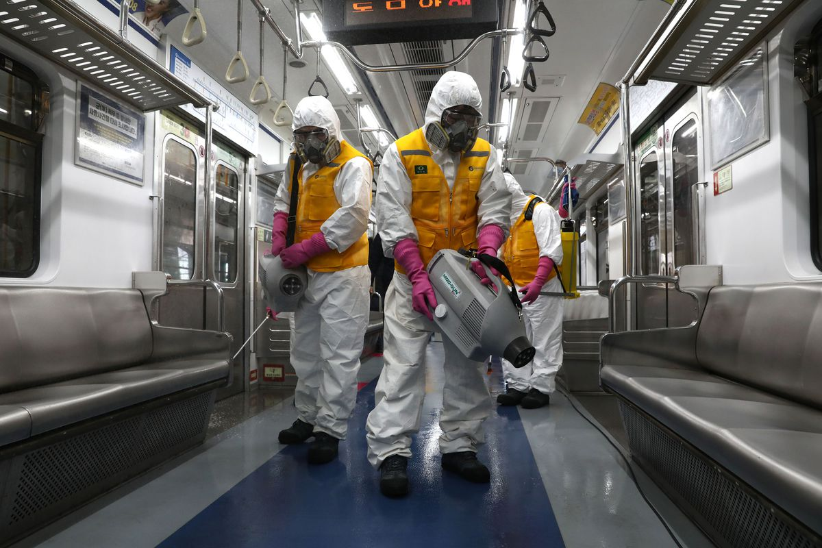 Disinfection workers wearing protective gear spray antiseptic solution against the coronavirus (Covid-19) in a subway cat at Seoul metro railway base.