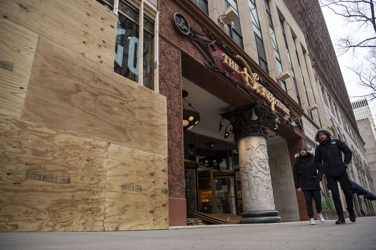 The Disney Store was boarded up Saturday as pedestrians walk in the 700 block of North Michigan Avenue.