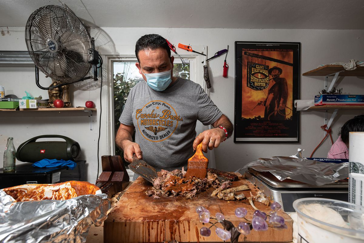 Ramon Coss at his barbacoa operation at his Richmond, California home spreading seasoning on the meat.
