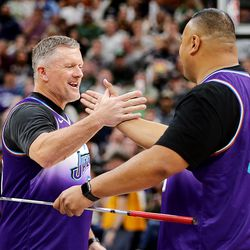 University of Utah head football coach Kyle Whittingham and BYU head football coach Kalani Sitake take part in a putting contest during a break in the game as the Utah Jazz and the Boston Celtics play an NBA basketball game at Vivint Smart Home Arena in Salt Lake City on Wednesday, Feb. 26, 2020. Boston won 114-103.
