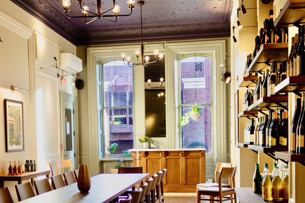 room with dining table and shelves with wine