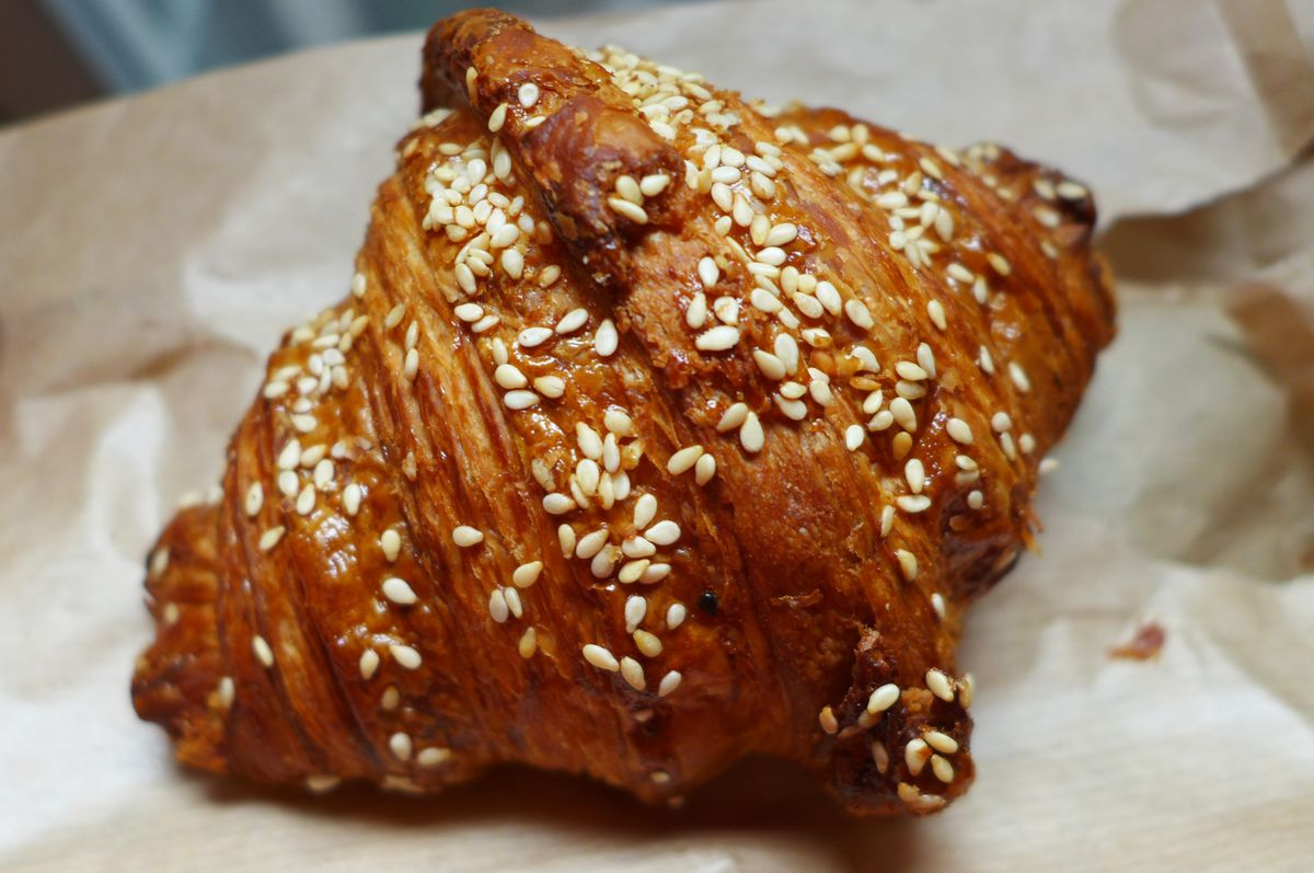 A croissant covered with sesame seeds.