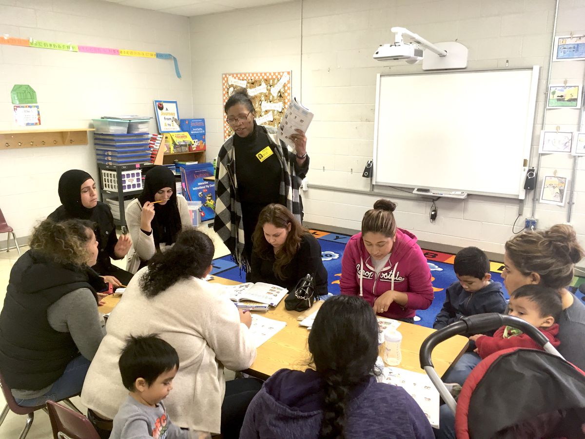 Volunteer teacher Alicia Hall leads an English class for parents at Kate Bond Elementary School.