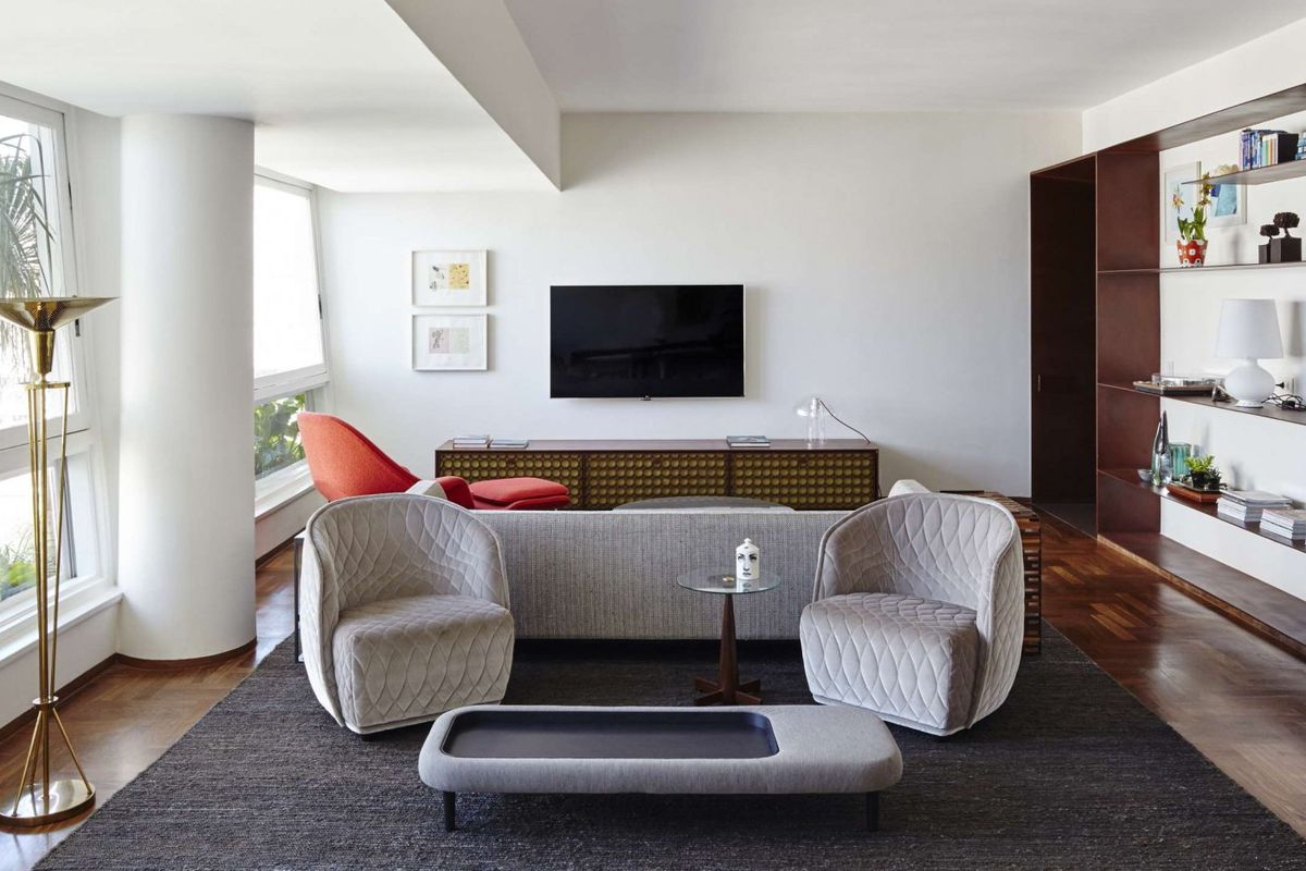 Interior shot of white-walled living room with a wall of windows on one side and Cor-Ten steel floating shelves on the other and modern furniture.