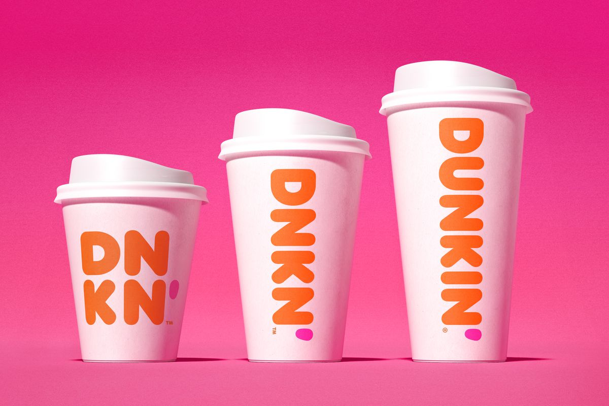 Three sizes of Dunkin' coffee cups, increasing in size left to right, on a pink background