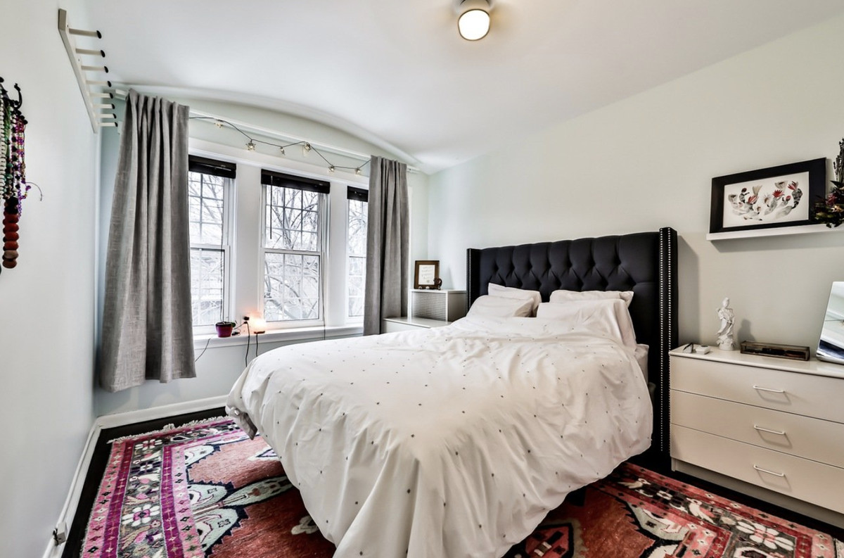 A bedroom with a large pink patterned carpet, thee windows, and an upholstered bed frame.