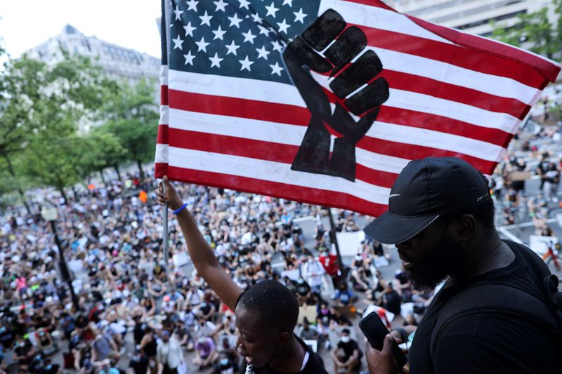 A black woman raises a US flag with a black fist stenciled on it. Below her is a crowd of what appears to be hundreds, if not thousands.