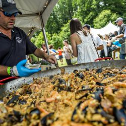 The Fox Bros. Bar-B-Q team offering paella from a giant skillet.