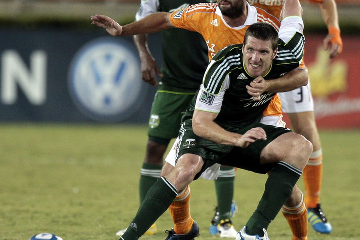 HOUSTON - AUGUST 14:  Kenny Cooper #33 of the Portland Timbers holds off Adam Moffat #16 of the Houston Dynamo as he looks to control a pass at Robertson Stadium on August 14, 2011 in Houston, Texas.  (Photo by Bob Levey/Getty Images)