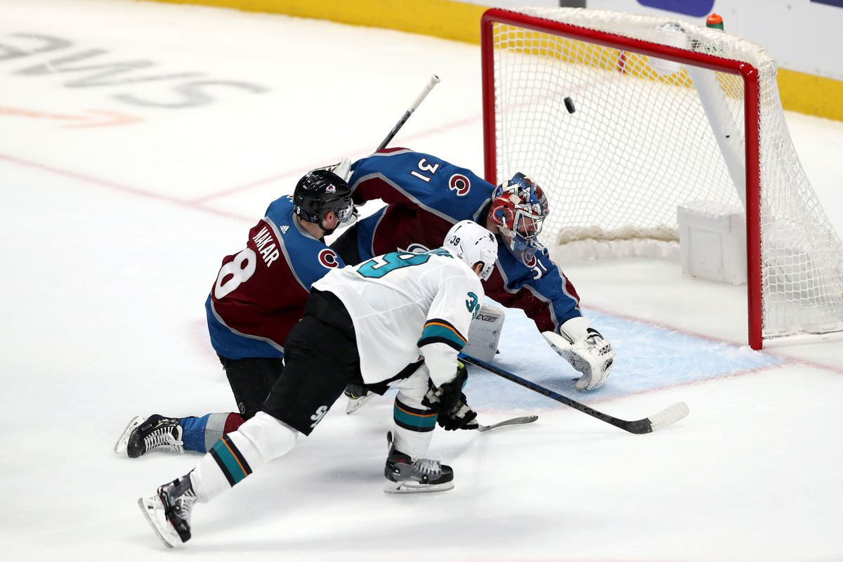 Logan Couture of the San Jose Sharks scores a goal past Cale Makar and goalie Philipp Grubauer of the Colorado Avalanche in Game 3 of the Western Conference Second Round during the 2019 NHL Stanley Cup Playoffs at the Pepsi Center on April 30, 2019 in Den