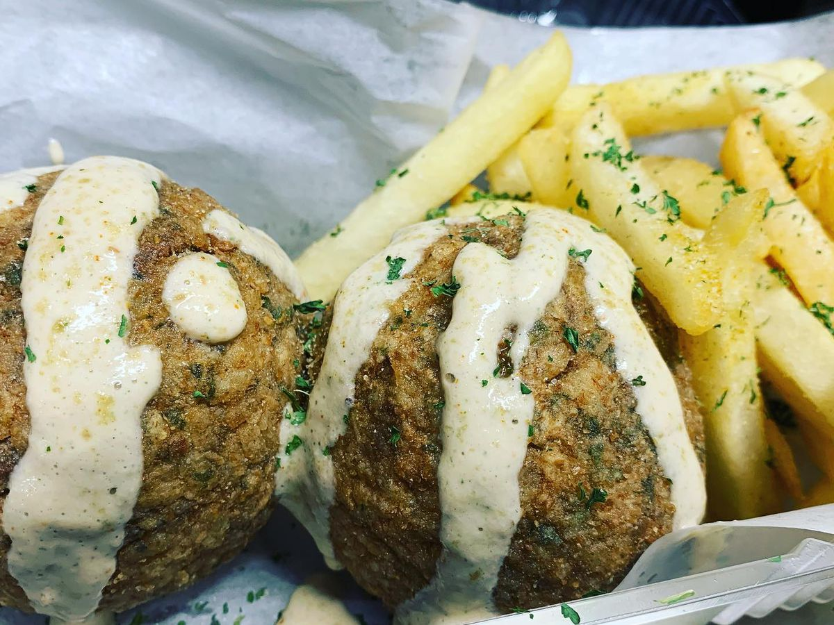 a plate of boudin balls next to a side of fries