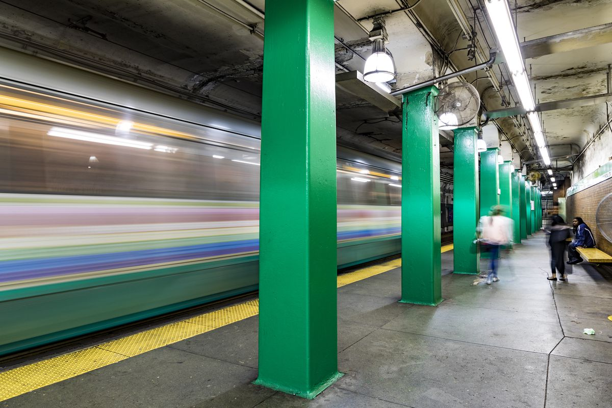 A subway platform in Boston with a train rolling through very fast.