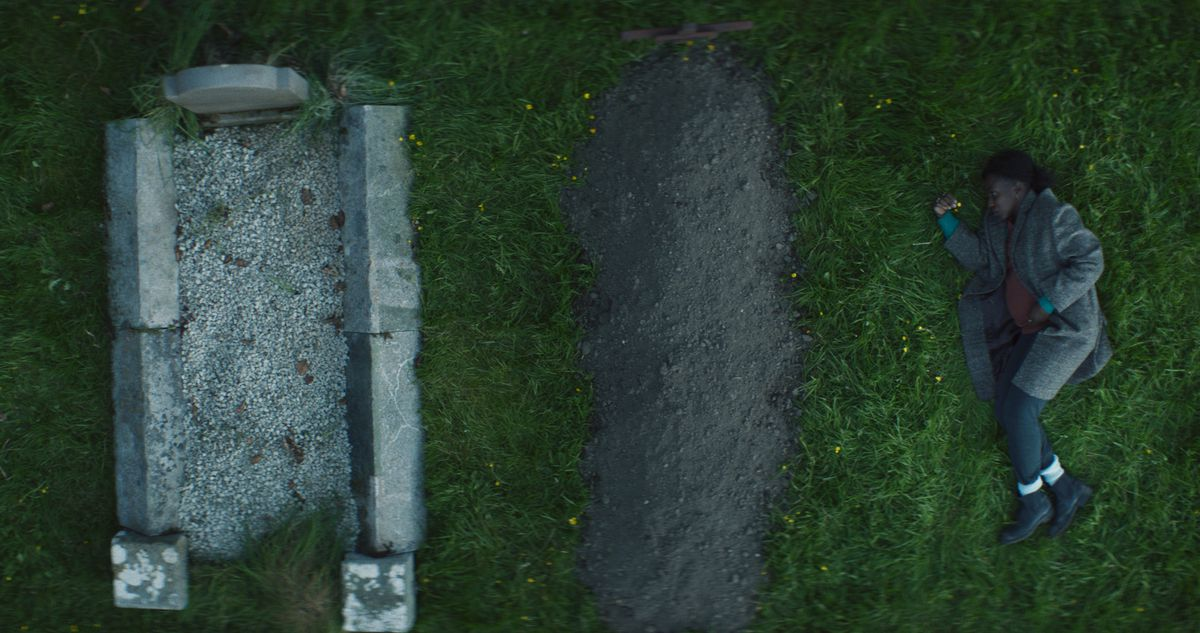 A heavily pregnant woman (Tamara Lawrance) lies in the grass next to two graves in Kindred