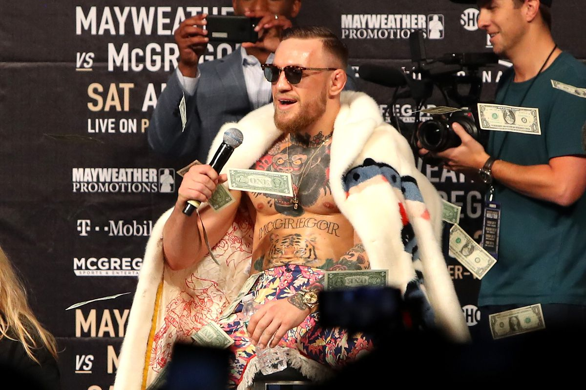 Conor McGregor takes questions amid a shower of bills during a press event.