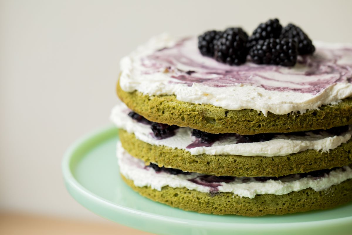 A side view of a matcha blackberry layer cake: the four green layers are sandwiched with whipped cream and mashed blackberries, and the top is covered with whipped cream and whole blackberries. The cake sits on a jade cake stand.