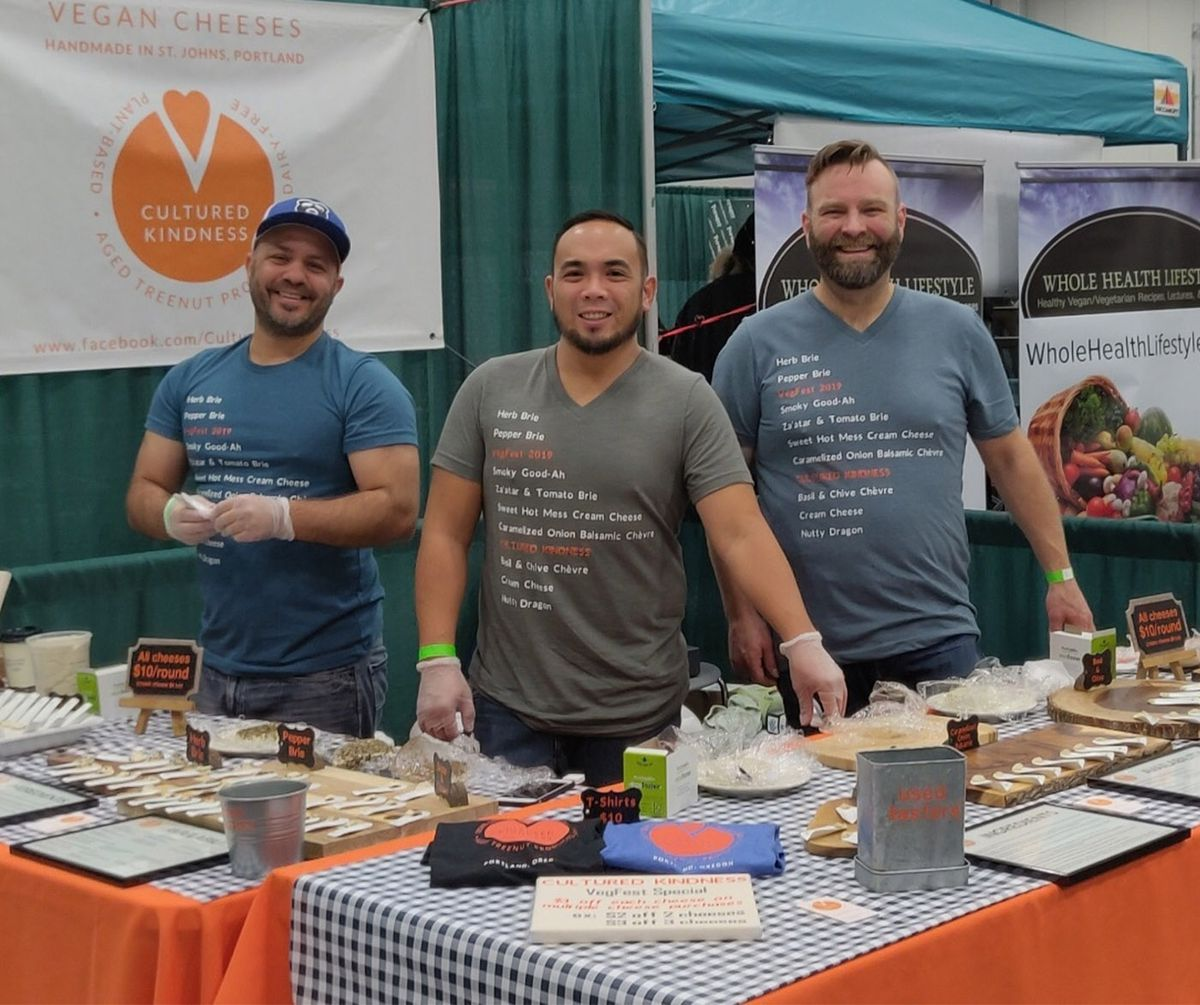 A photo of the Cultured Kindness team at VegFest 2019 with a table of cheese samples and t-shirts