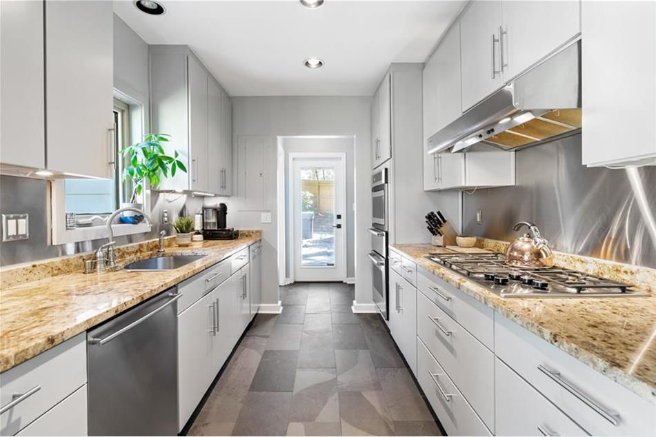 A long white kitchen with a window door at the end.