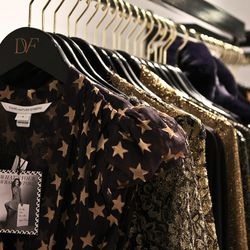 Pieces from DVF's latest ready-to-wear collection hang on branded branded hangers hinged onto wall shelves.