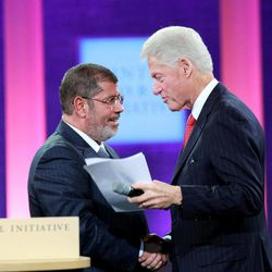 Former U.S. President Bill Clinton, right, greets Egyptian President Mohammed Morsi at the closing session at the Clinton Global Initiative in New York Tuesday, Sept. 25, 2012