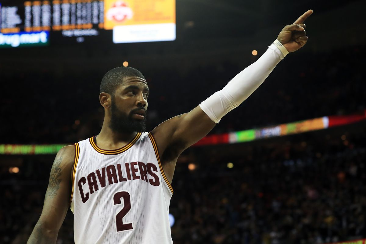 Cleveland Cavalier Kyrie Irving stands on the court with one arm raised