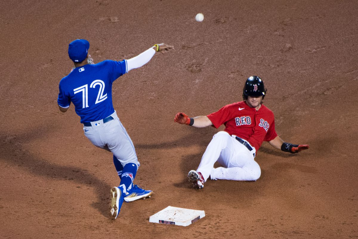 Andrew Benintendi #16 of the Boston Red Sox safest slides into second base while Santiago Espinal #72 of the Toronto Blue Jays is unable to make the tag in the seventh inning at Fenway Park on July 21, 2020 in Boston, Massachusetts.