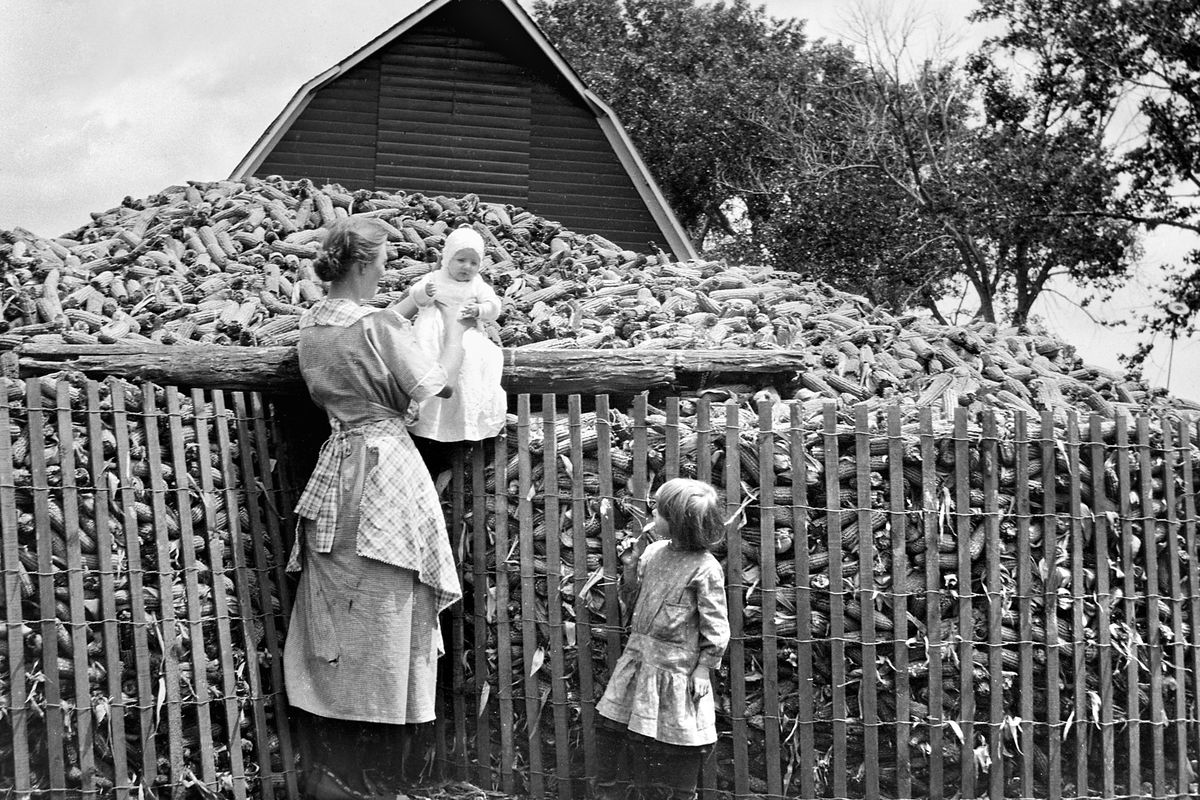Young mother with her children next to the corn crib, ca.1925