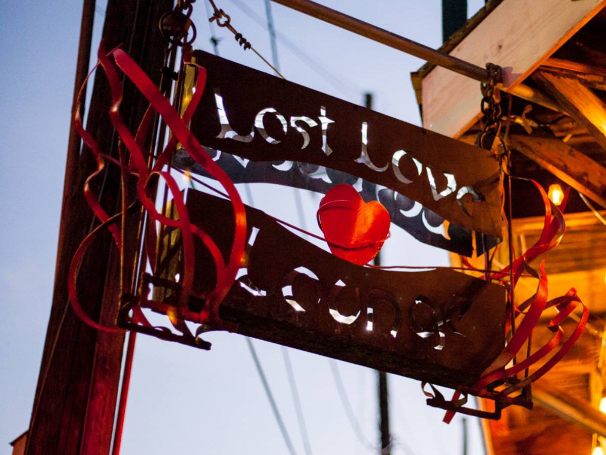 A cut-out iron sign hanging from a telephone pole reads Lost Love Lounge