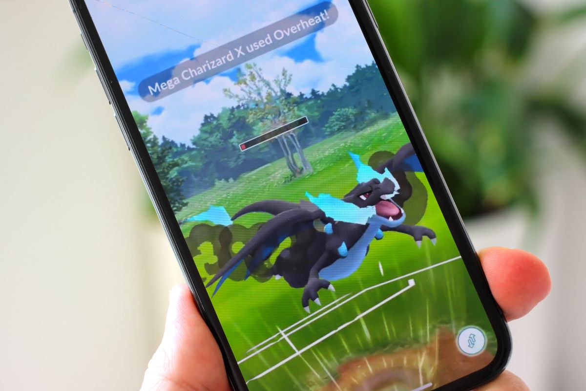 A photo of an iPhone displaying a Mega Charizard from Pokémon Go