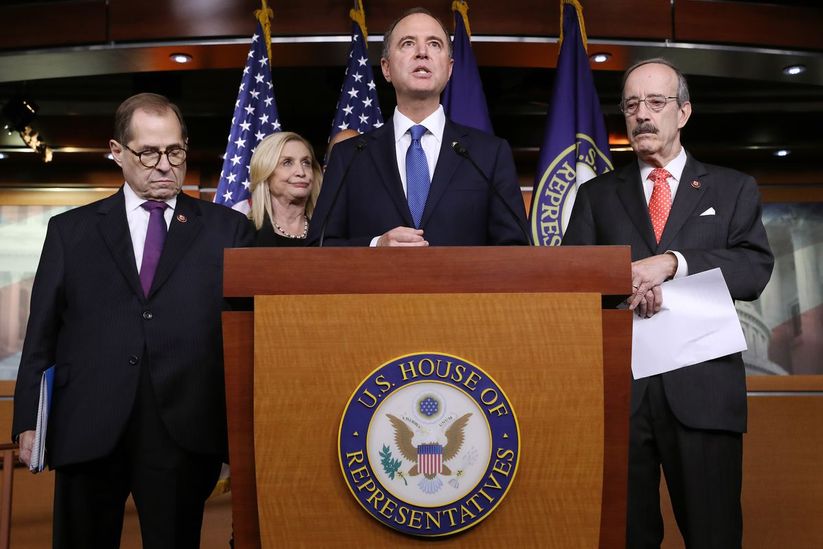 House Democrats stand behind a podium at a press conference.