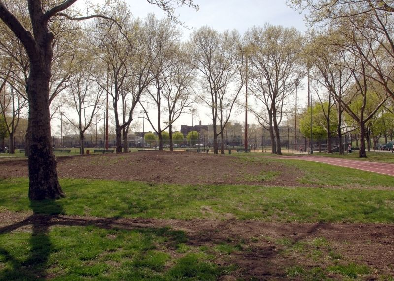 A park with a green lawn, large patches of dirt, and trees.