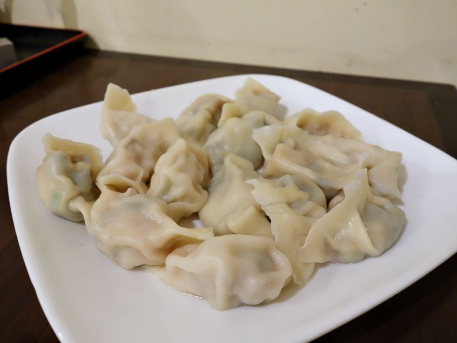 A white plate filled with boiled dumplings from Little Ting's.