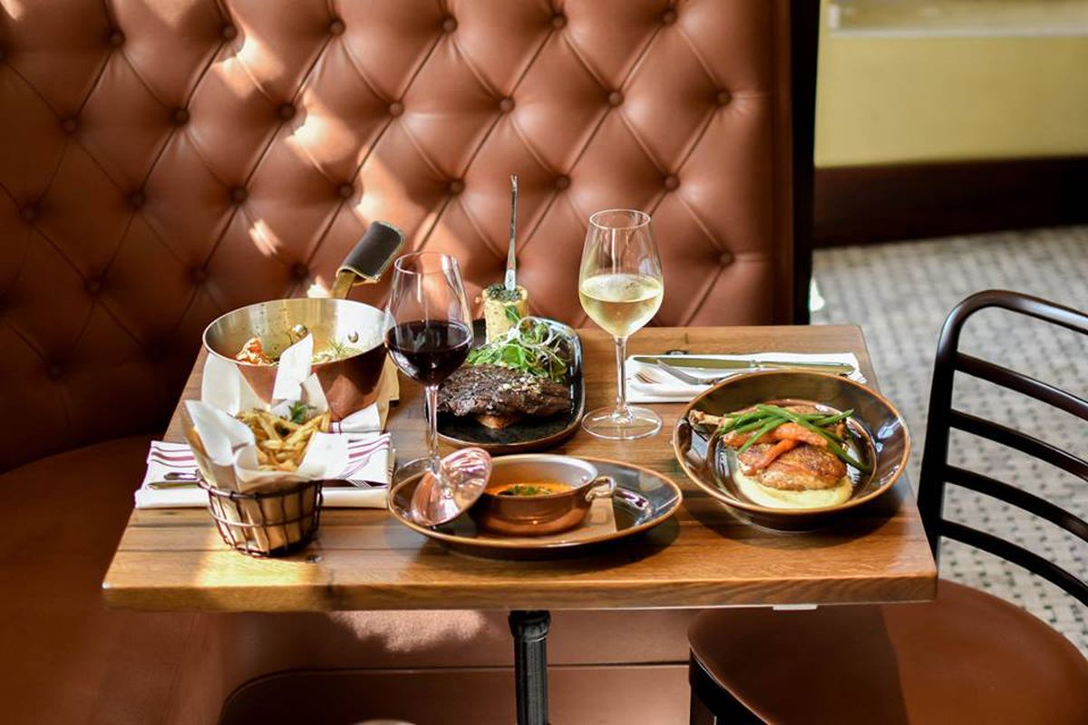 A variety of French dishes sit on a restaurant table in front of a mauve leather booth.