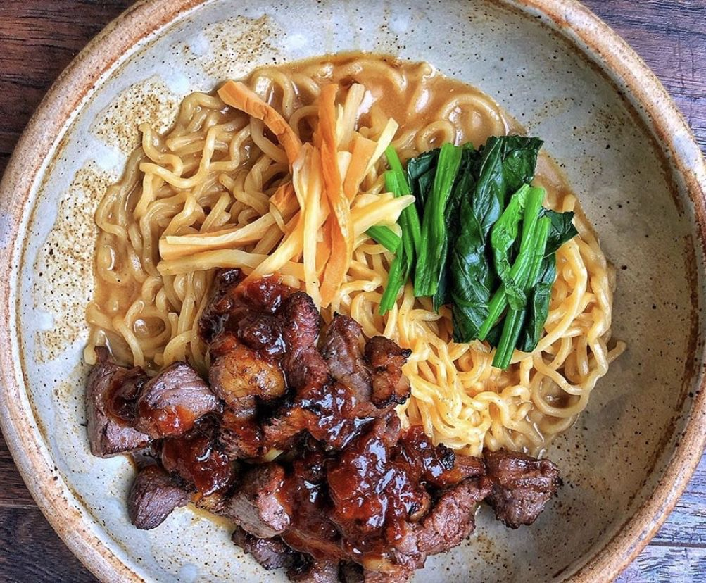Ramen noodles topped with chunks of steak and greens