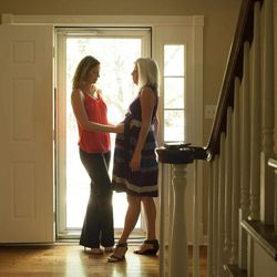 Emily Jordan, left, examines the pregnant belly of her mother Cindy Reutzel on Sunday, Aug. 19, 2012 in Naperville, Ill. After Jordan underwent a radical hysterectomy, she and her husband took up an offer from Reutzel to act as a surrogate for their child.