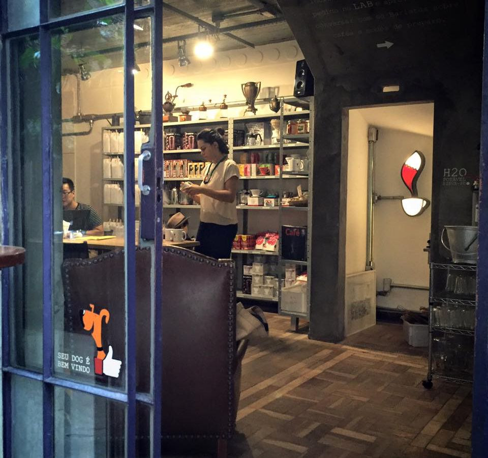 The interior of a cafe, with several customers walking in the room or sitting, and a bookshelf in the back filled with items for sale and coffee equipment
