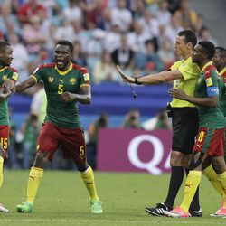 Cameroon players protest with referee Wilmar Roldan during the Confederations Cup, Group B soccer match between Germany and Cameroon, at the Fisht Stadium in Sochi, Russia, Sunday, June 25, 2017.