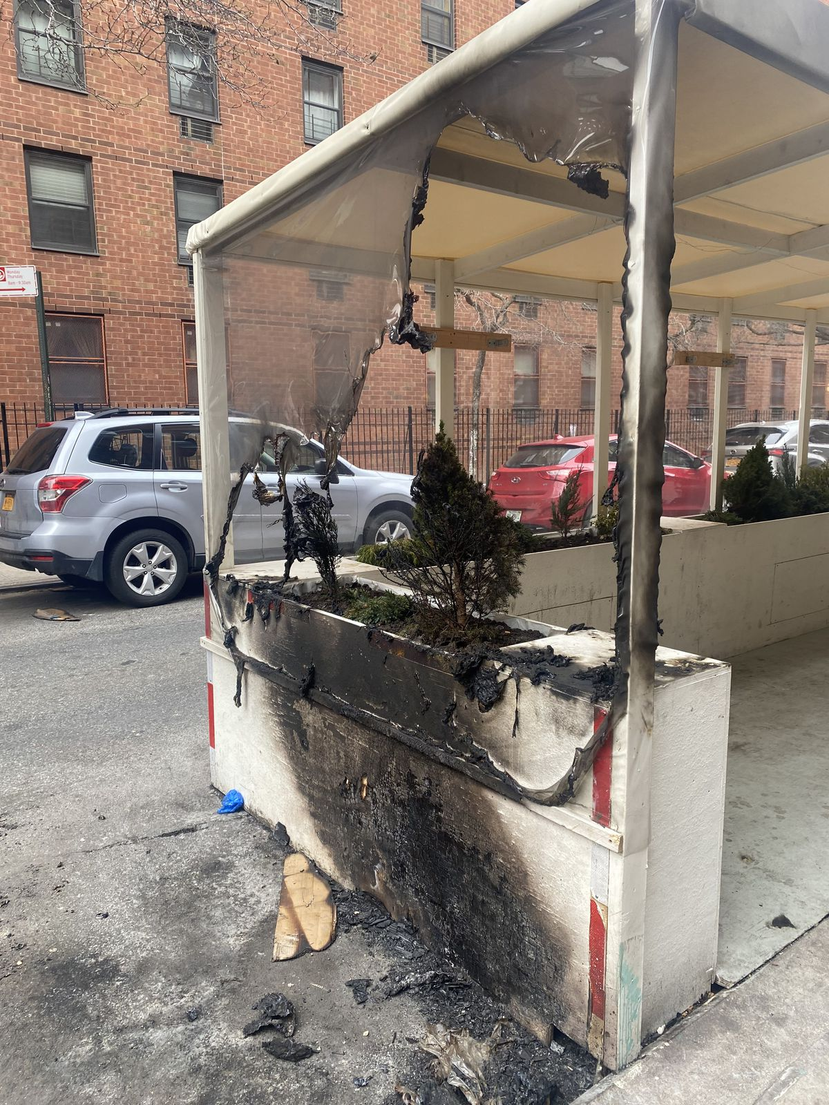 A wooden outdoor dining setup is destroyed after what appears to be a recent fire