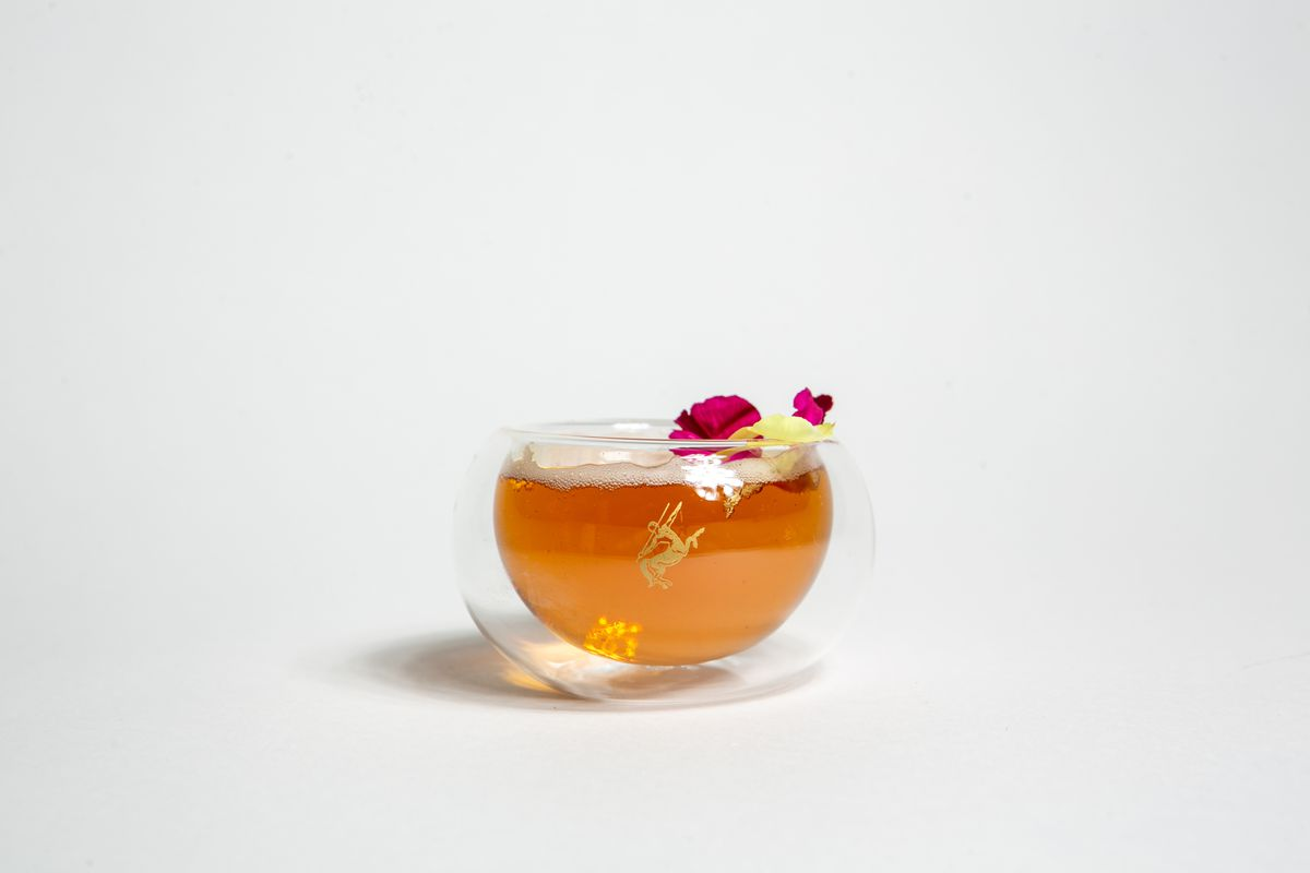 """The """"Tea for Yu"""" Rémy Martin cocktail, in a glass teacup and topped with small flowers."""